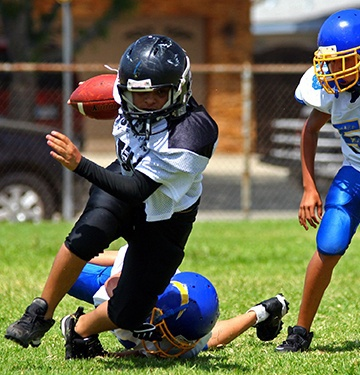 Young boy placing blue sports mouthguard