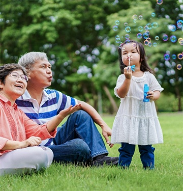 grandparents in a park with their grandchild